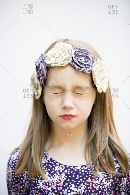 Girl with eyes closed wearing flower headband on white background