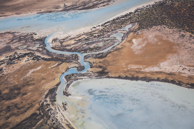 Aerial view of river cutting through arid sands and emptying into  Shark Bay, Australia