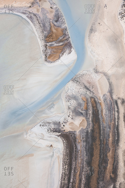 Top down view of river cutting through sandbar sands and emptying into ocean in Shark Bay, Australia