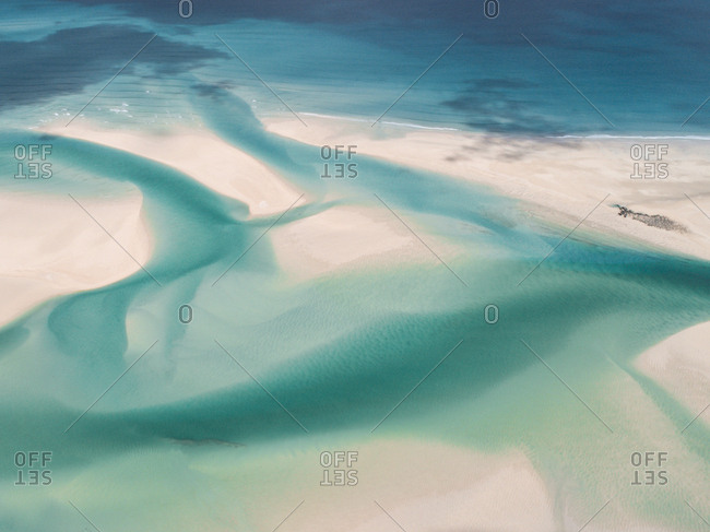 Looking down on turquoise sea cutting channels  through soft white sands in Broome, Australia