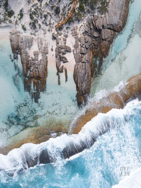 Aerial view of ocean crashing against rocky coastal shelf  off Denmark, Australia