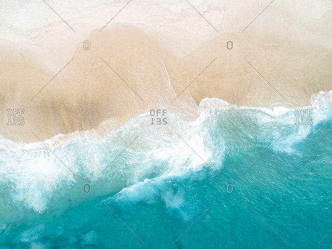 Aerial view of waves gently breaking against soft white sands of Denmark, Australia