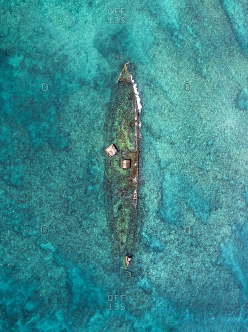 Aerial view of wrecked ship half submerged in crystal clear waters off Exmouth, Australia