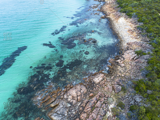 Aerial view of vegetation of bush pushing up against rocky shoreline of Meelup, Australia