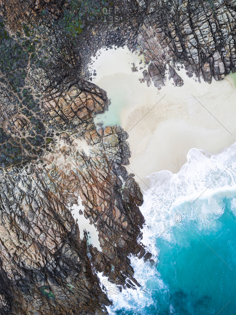 Aerial view of sea lapping at white sand beach protected by rock formations in Yallingup, Australia