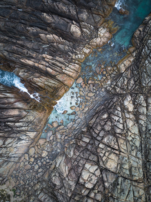 Aerial view of narrow channel carved out of rocky sea on coast of Yallingup, Australia