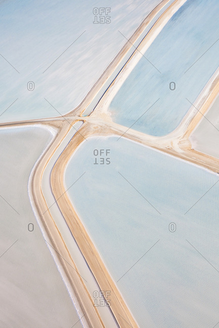 Aerial view of access roads undulating through milky salt fields in Shark Bay, Australia