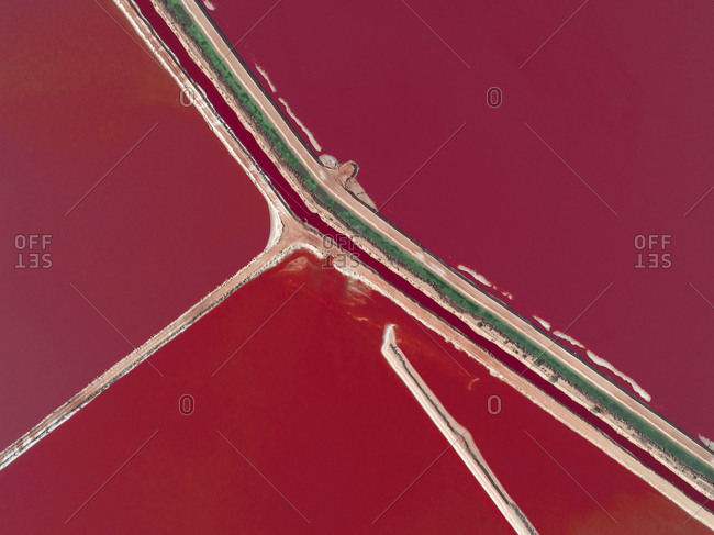 Aerial view of access roads separating bright red salt fields in Western Australia