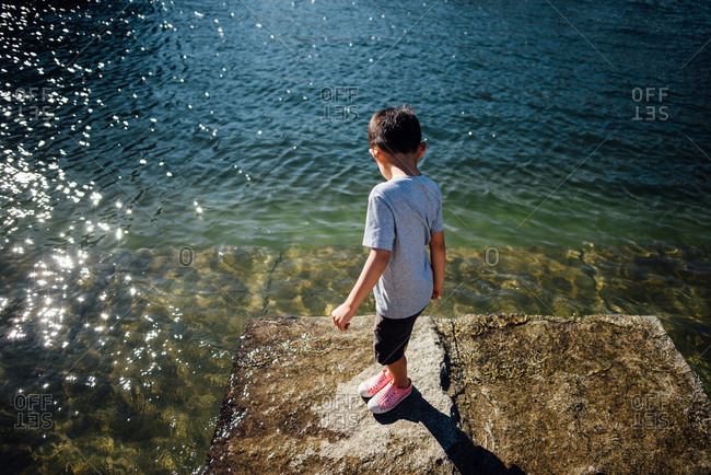 Boy standing on rock as tide comes in