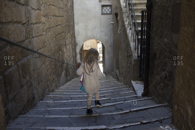 Young girl with her doll adventuring down a narrow street in Pitigliano