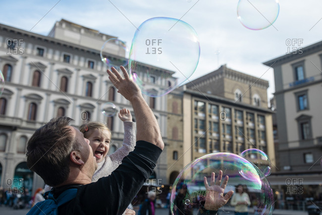 FLORENCE, ITALY - OCTOBER 31: Children react to a busker producing bubbles in the Piazza della Republica