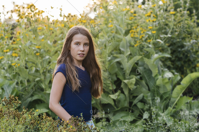Portrait of confident girl with long brown hair standing in a field of flowers