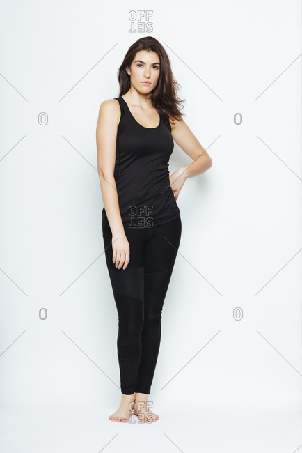 Full length portrait of confident woman in sportswear standing with hand on hip over white background