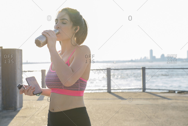 Tired young woman drinking water after workout on street during sunny day