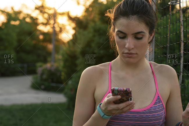 Close-up of young woman in sports bra using mobile phone in park during sunset