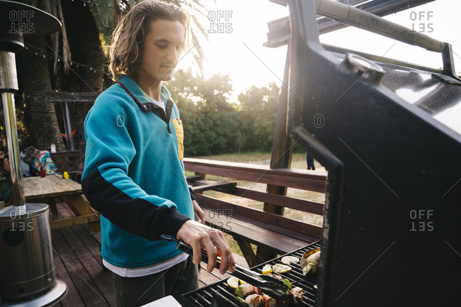Young man preparing kebabs on barbeque grill in yard