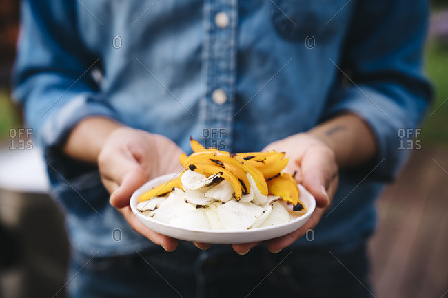 Midsection of woman holding plate of chopped grilled vegetables outdoors