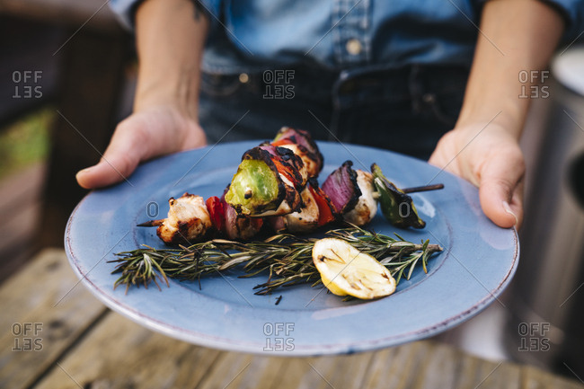 Midsection of woman holding plate of grilled kebab and rosemary outdoors