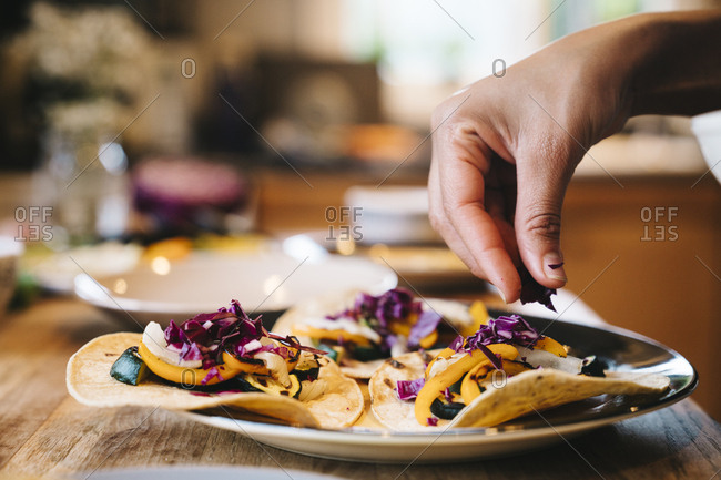 Close-up of woman's hand preparing taco with chopped red cabbage at table