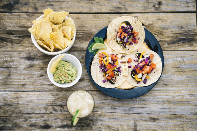 Directly above shot of delicious Mexican tacos and nachos on wooden table