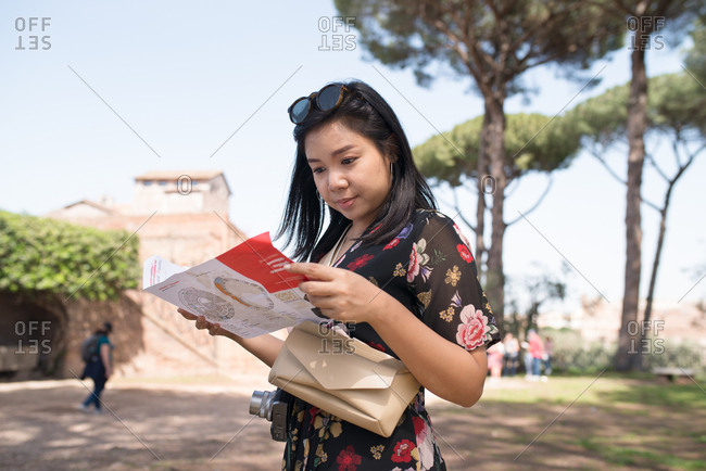 Rome, Italy - April 8, 2018: Young woman looking at brochure while travelling