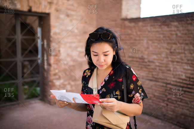 Young woman looking at brochure while travelling in Rome