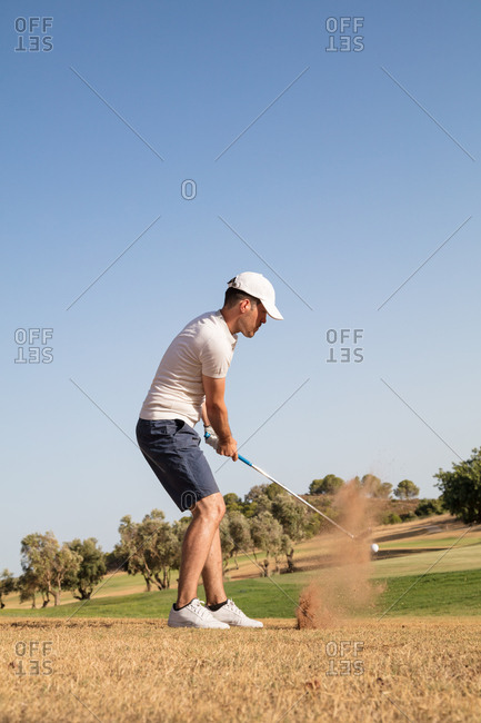 A man hitting golf ball with dust impact