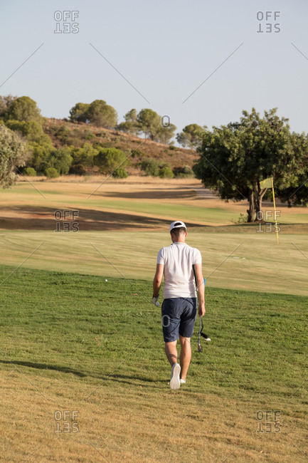 Golf player walking towards ball