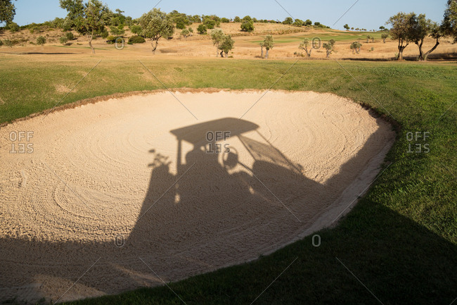 Golf cart shadow in sand bunker