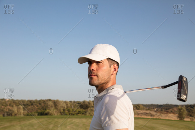 A man watches his drive on a golf course