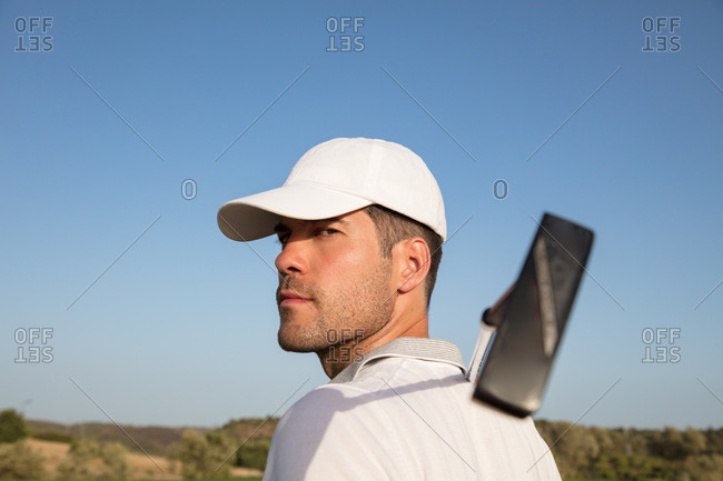 Golf player with club looking into camera