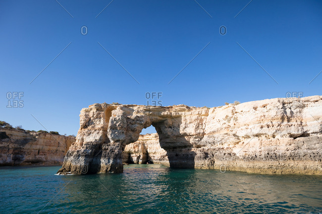 Natural rock arch in the waters of the albandeira Beach in Algarve, Portugal