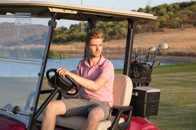 Young handsome golfer driving golf cart with bag of clubs
