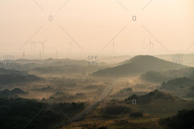 Sunrise above a highway and wind turbines, Jejune Island