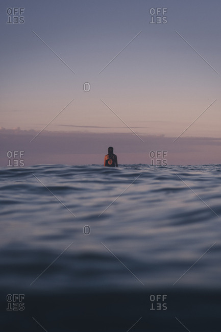 Rearview of female surfer in water waiting for waves