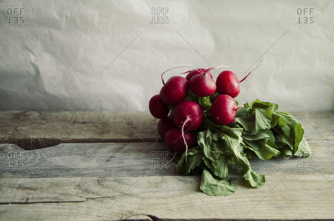 Heap of fresh radishes with tops and leaves on wooden rustic background with copy space