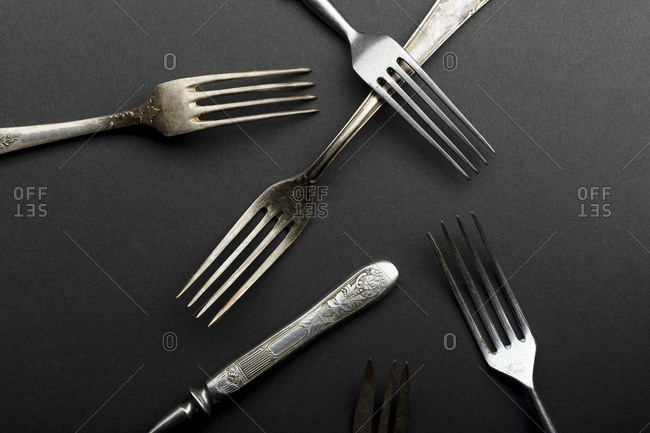 Vintage metallic cutlery and kitchen utensils on gray background