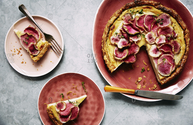 Creamed roasted cauliflower and fennel tart with watermelon radish slices on top.