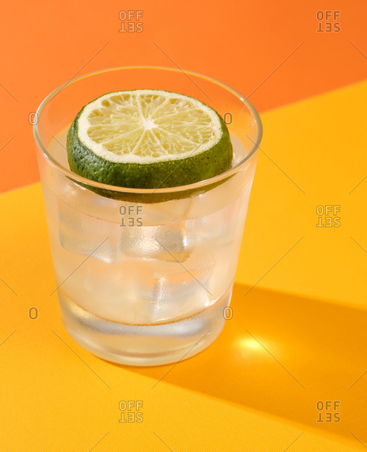 Limeade topped with slice of lime on orange and yellow studio backdrop