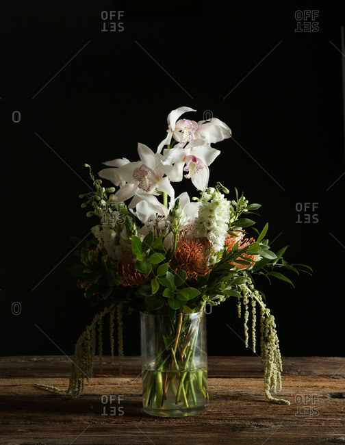 Floral arrangement with orchids on dark background and rustic table