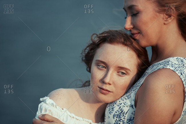 Mother and daughter hugging at the ocean