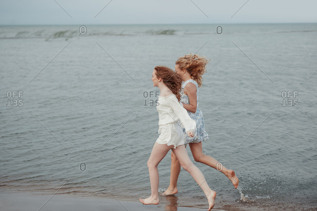 Mother and her teenage daughter running along the beach