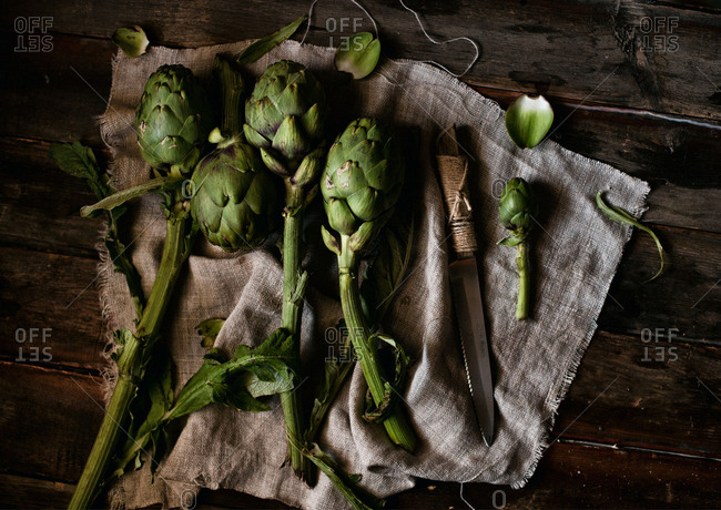 Raw artichokes and a knife on a cloth over wooden surface