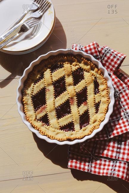 Italian crostata pie with jam on wooden table outdoor