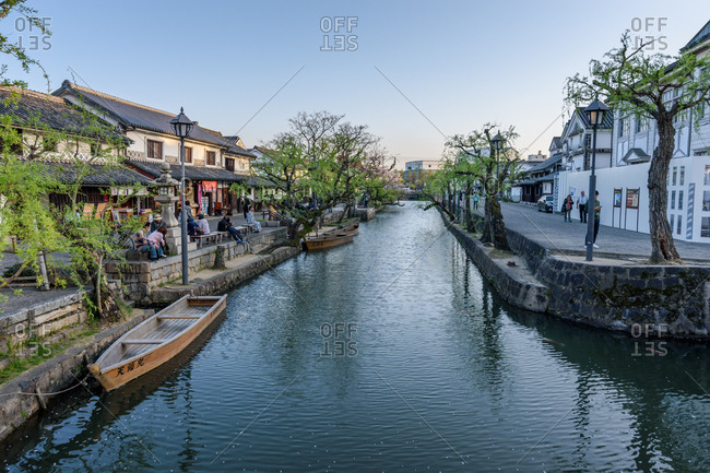 Kurashiki, Japan - April 04, 2018: People enjoying a balmy spring evening on by the river in the historic quarter of the city