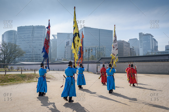 Seoul, South Korea - April 09, 2018: Traditional changing of the guard ceremony at Gyeongbokgung Palace with very modern cityscape in background