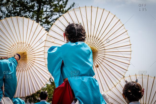 Japanese women in traditional kimonos holding parasols towards sky