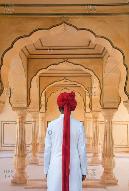 Rear view of tour guide in traditional dress framed by arches in the Amber Fort in Rajasthan, India