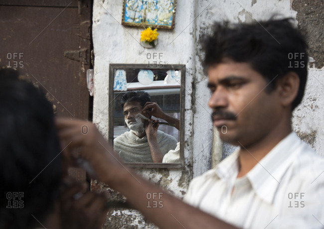 Mumbai, India - October 02, 2013: A man getting a shave with a straight razor at an outdoor barber