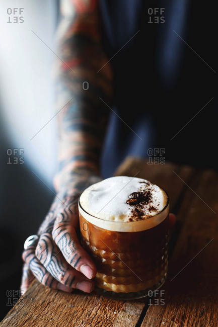 Man with fully tattooed arm holding cup of coffee on wooden table